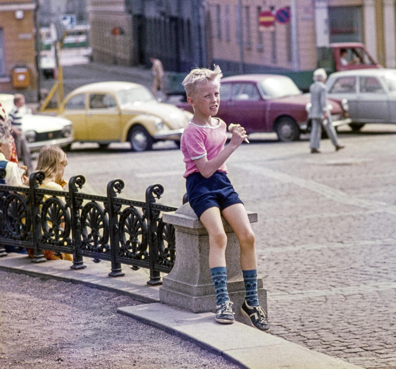 Poika syö jäätelöä ja istuu Aleksanteri II:n patsasta ympäröivän koristekaiteen tolpan päällä, taustalla Sofiankatu Kuvaaja: Punkari Pekka, Kuvanottovuosi: 1977