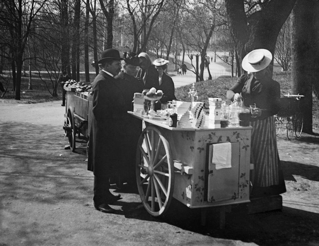 Helsingin muinaismuistolautakunta ja Signe Brander (keskellä) sunnuntairetkellä Kaisaniemessä virvokkeiden myyntikärryn luona. Kuva: Reinhold Hausen 1907