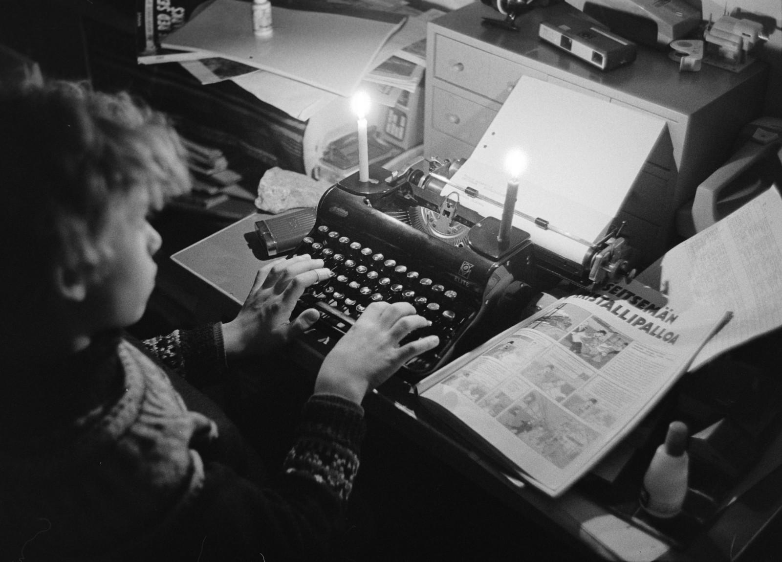 Poika kirjoittaa mekaanisella kirjoituskoneella kynttilänvalossa. Kuva: Helsingin kaupunginmuseo/Lauri Pietarinen, 1970-luku.
