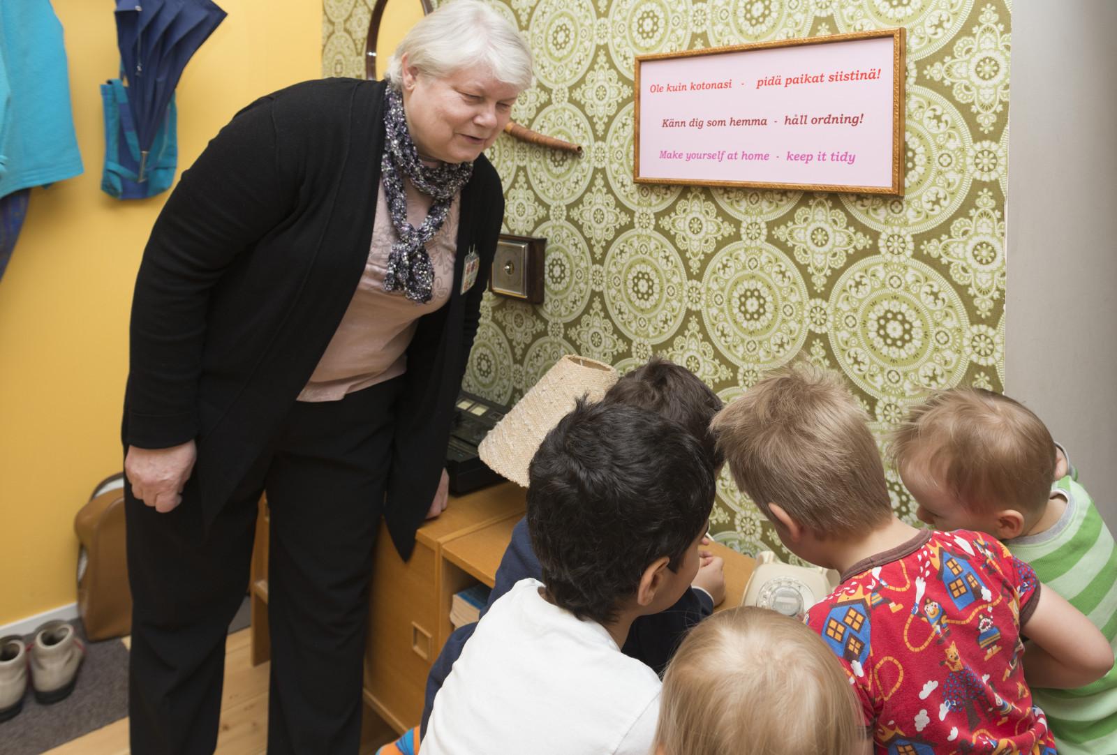 Mummolan lankapuhelin kiinnostaa lapsia kovasti, kertoo museomummo Pirjo Järvimäki. Kuva: Helsingin kaupunginmuseo/Juho Nurmi.