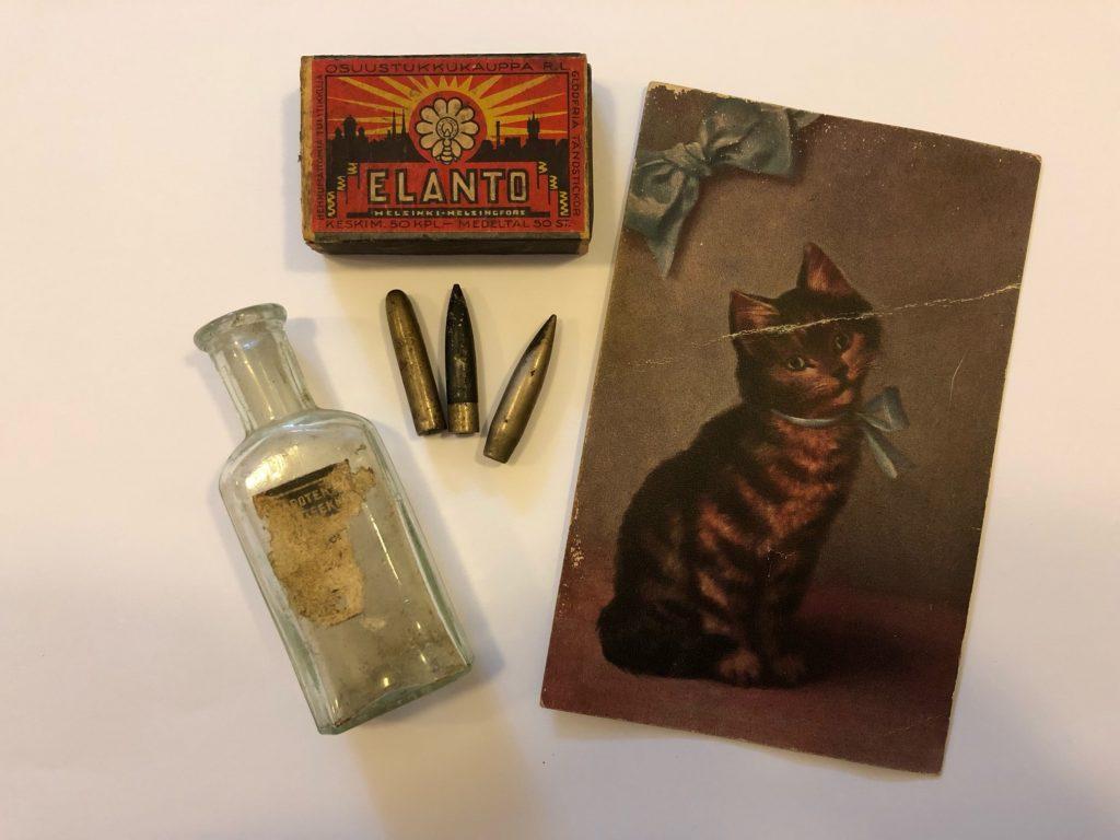 Vanhoja tavaroita: postikortti, tulitikut, lasipullo